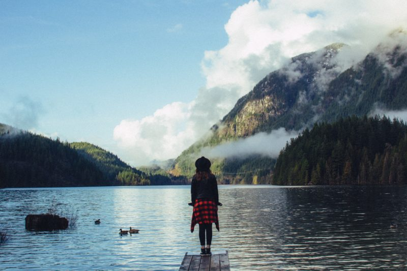 Girls stands at endge of Canadian mountain lake